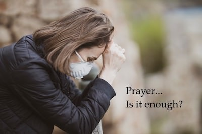 Woman with a mask praying outside. Is prayer enough? Kathleen Robison, author, shares her experiences with prayer.